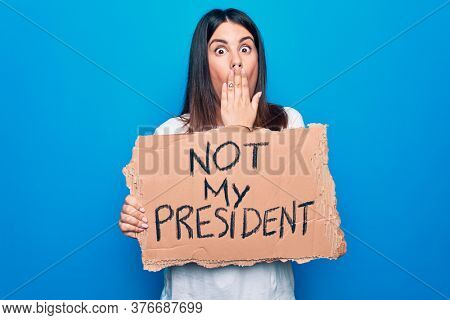 Young beautiful woman on disagreement holding banner with not my president message covering mouth with hand, shocked and afraid for mistake. Surprised expression