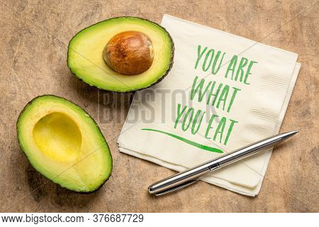 healthy eating and lifestyle concept - you are what to eat reminder words handwritten on a napkin with cut avocado fruit