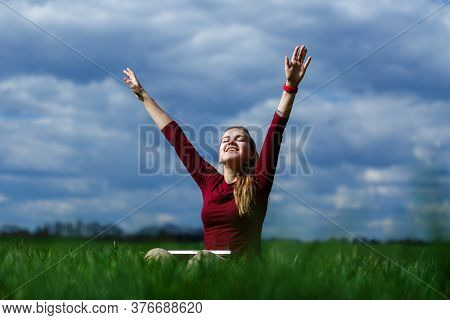 Young Successful Woman Is Sitting On Green Grass With A Laptop In Her Hands. Rest After A Good Worki