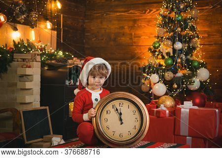 Happy Kid Is Wearing Santa Clothes, Sitting By The Big Clock. Kid Santa With Alarm Clock Christmas.