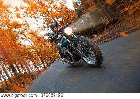 Motorcycle driver riding in autumn forest, blur motion effect