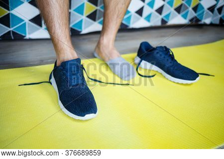 Guy Man Shoes Sport Shoes Standing On A Yellow Rug For Sports, Training At Home