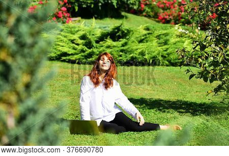 Red Head Young Woman. Spring Beautiful Romantic Red Haired Girl In Spring Garden. Young Model Lookin