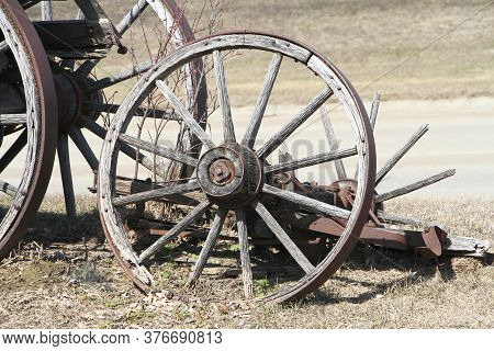 A Wooden Wagon Wheel With Wood Spokes Medal Rim And Wood  Hub.