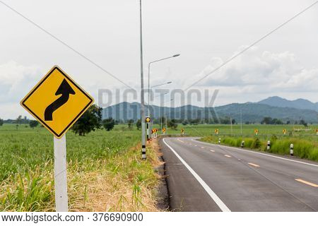 Sign Curved Road On The Way At The Natural  Field Or Meadow. Warning Attention Right Curve Sign At R