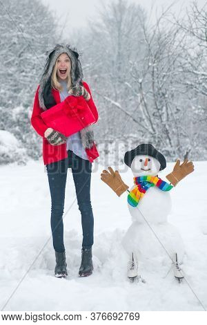 Joyful Girl Having Fun With Snowman In Winter Park. Winter Background With Snowflakes And Snowman