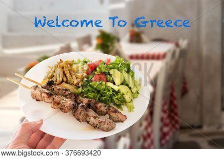 A Traditional Greek Pork Souvlaki Plate Over A Tavern Background. Welcome To Greece Concept.