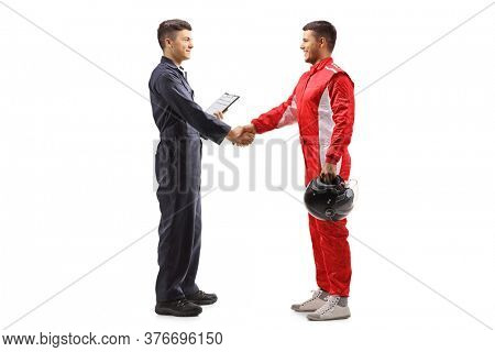 Full length profile shot of an auto mechanic shaking hands with a racer isolated on white background