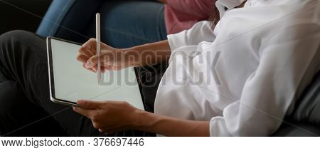 Female Using Mock Up Tablet With Stylus On Her Lap While Sitting Near Her Friend On Sofa