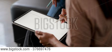 Female Using Mock Up Tablet With Stylus Pen While Sitting On Sofa In Living Room