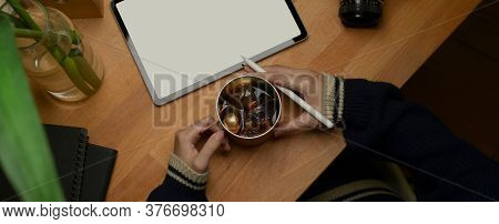 Female Hands Holding Ice Coffee Mug And Stylus Pen While Working With Mock Up Tablet On Wooden Table