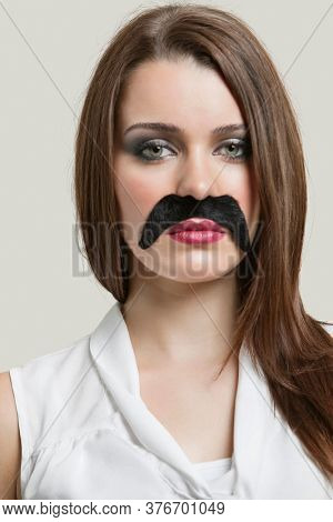 Portrait of serious young woman with fake mustache over gray background