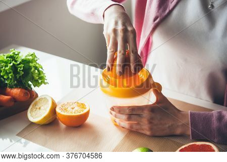 Young Woman Squeezing Juice From Orange In The Kitchen Using A Squeezer