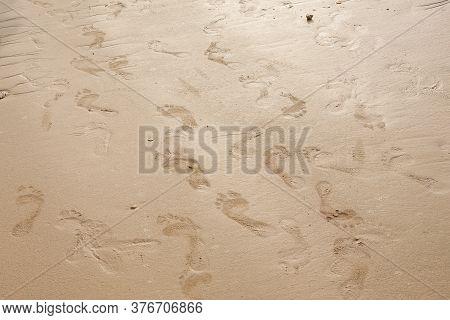 Footprints On The Beach Sand.