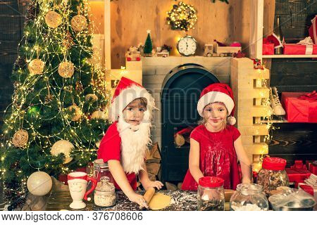 Happy Children Bake And Decorate Christmas Cookies. Funny Kids In Kitchen Making Christmas Cookies.