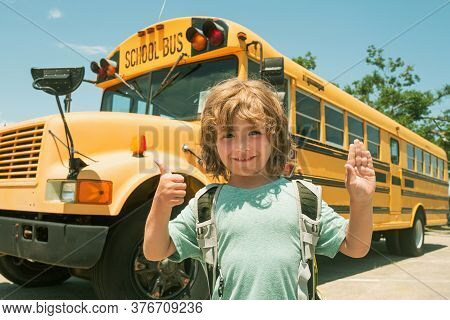 Child From Elementary School With Bag On School Bus Backgroung. Happy School Children