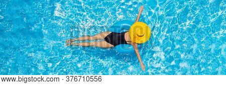 Woman Sitting In A Swimming Pool On A Ring Pool Float In A Large Yellow Sunhat Banner, Long Format