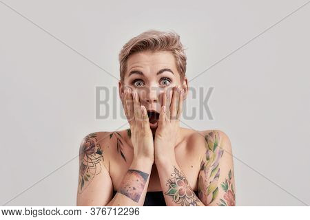 Portrait Of Amazed Tattooed Woman With Short Hair Looking Amazed Or Shocked At Camera With Open Mout