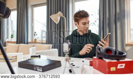 Young Male Technology Blogger Recording Video Blog Or Vlog About New Tablet Pc And Other Gadgets At