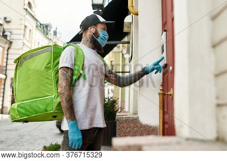 Brutal Bearded Delivery Man In Cap Wearing Mask Due To The Emergence Of The Covid19 Virus, Ringing A