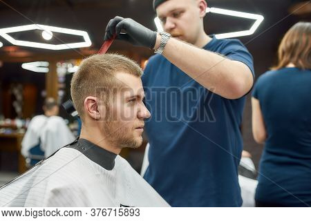 Professional Tattooed Barber Making Modern Haircut For A Young Handsome Guy Sitting Sitting Barbersh