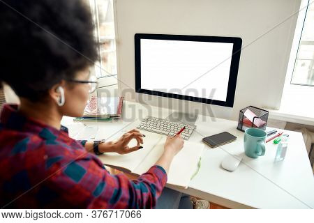 Rear View Of Afro American Woman Sitting At Her Workplace At Home And Studying Online. Using Compute