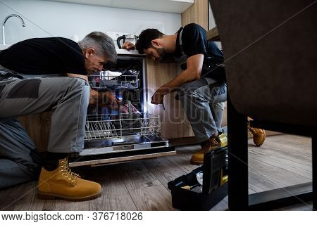 Aged Repairman Fixing Dishwasher In The Kitchen, Using Screwdriver While His Colleague In Uniform He