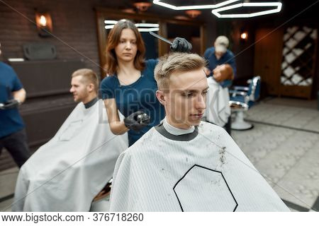 Visiting Hair Stylist In Barbershop. Young Barber Girl Working With Hair Clipper, Making Modern Hair