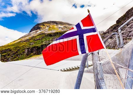 Norwegian Flag Against Utsikten Viewpoint At Gaularfjellet. Tourist Attraction. Scenic Route In Norw