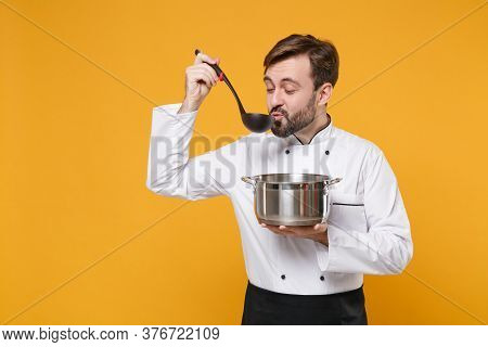 Young Bearded Male Chef Cook Or Baker Man In White Uniform Shirt Posing Isolated On Yellow Backgroun