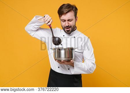 Irritated Young Bearded Male Chef Cook Or Baker Man In White Uniform Shirt Posing Isolated On Yellow