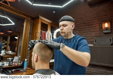 Working Process. Professional Barber Serving Client, Making Trendy Haircut For Young Caucasian Man V
