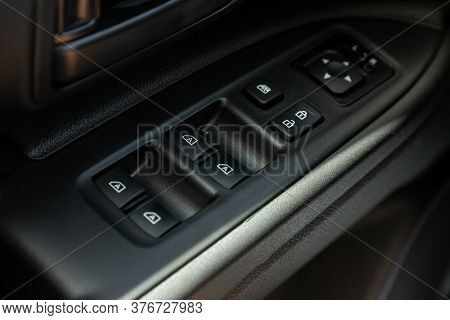 Closeup Of A Door Control Panel In A New Car. Arm Rest With Window Control Panel, Door Lock Button,