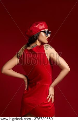 Gorgeous Brunette Woman In White Sunglasses, Leather Beret And Dress Posing In Studio On Red Backgro