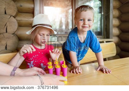 Two Cute Adorable Caucasian Blond Little Sibling Sitting At Table Home Yard And Have Fun Tasting Mom