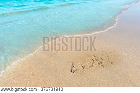 Love Word Hand Writting Letter On Brown Sand Beach Near Small Wave Of Blue Water In The Sea
