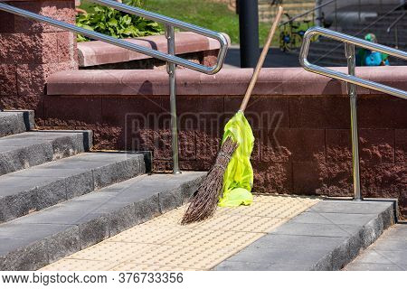 Broom, Standing On The Sidewalk, Steps. The Concept Of A Clean City. The Problem Of Migrants, Crisis