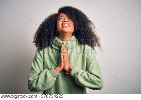 Young beautiful african american woman with afro hair wearing green winter sweater begging and praying with hands together with hope expression on face very emotional and worried. Begging.