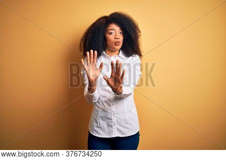 Young beautiful african american elegant woman with afro hair standing over yellow background Moving away hands palms showing refusal and denial with afraid and disgusting expression. Stop