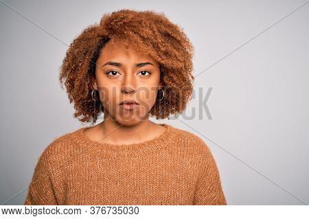 Young beautiful African American afro woman with curly hair wearing casual sweater with a confident expression on smart face thinking serious
