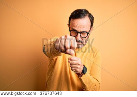 Middle age hoary man wearing casual sweater and glasses over isolated yellow background Punching fist to fight, aggressive and angry attack, threat and violence