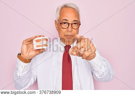 Middle age senior grey-haired dentist man holding prosthesis denture over pink background pointing with finger to the camera and to you, hand sign, positive and confident gesture from the front