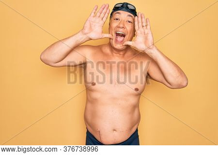 Middle age senior grey-haired swimmer man wearing swimsuit, cap and goggles Smiling cheerful playing peek a boo with hands showing face. Surprised and exited