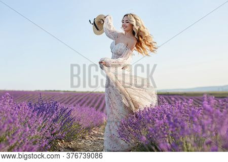 Pretty Blonde Woman Running Away In Lavender Field. Woman In Long Dress And Straw Hat Having Fun In