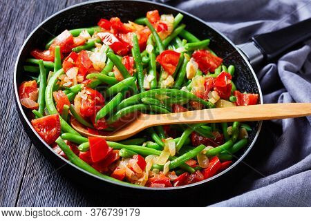 Close-up Of Skillet Fried Green Beans With Onions And Tomatoes, Fry Bodi In A Skillet On A Wooden Ta