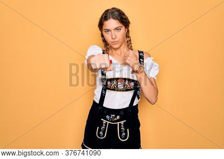 Young beautiful blonde german woman with blue eyes wearing traditional octoberfest dress Punching fist to fight, aggressive and angry attack, threat and violence