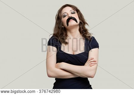 Young woman with arms crossed wearing fake mustache over gray background