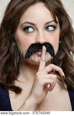 Close-up of young woman with finger on lips wearing fake mustache