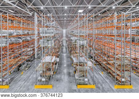 Large Warehouse. Tall Metal Shelves Filled With Various Boxes, Containers And Drawers.