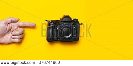 Modern Slr And Mirrorless Camera In Male Hands On Yellow Background Flat Lay Copy Space. Digital Pho